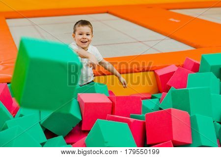 The boy throws himself in a dry pool with bright soft cubes