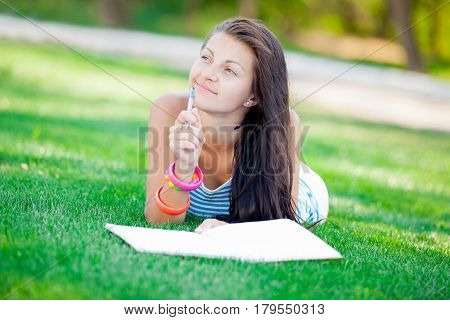 photo of young girl lying on the grass and thinking about something