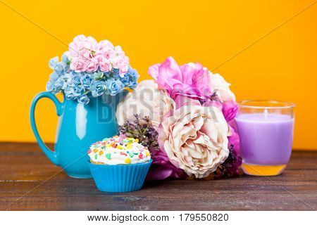 Photo Of Tasty Glazed Donut Near Wonderful Flowers In Vase And Candle On The Wonderful Yellow Backgr