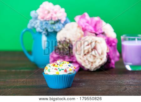 Photo Of Tasty Glazed Donut Near Wonderful Flowers In Vase And Candle On The Wonderful Green Backgro