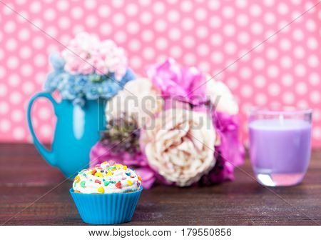Photo Of Tasty Glazed Donut Near Wonderful Flowers In Vase And Candle On The Wonderful Pink Dotted B