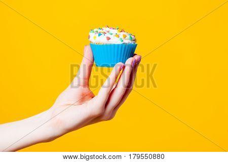 Photo Of Female Hand Holding Cupcake On The Wonderful Yellow Background