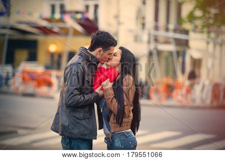 Photo Of Cute Couple Holding Heart Shaped Pillow And Kissing On The Wonderful Street Background