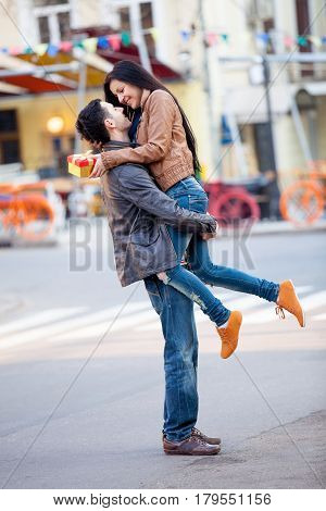Photo Of Cute Couple Holding Gift And Hugging On The Wonderful Street Background