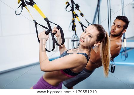Photo of handsome man and beautiful woman. Sporty people training with TRX Suspension at fitness club. They looking at camera