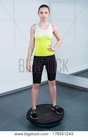 Photo of beautiful young sporty woman. Fitness girl working out with bosu at fitness club. Woman looking at camera