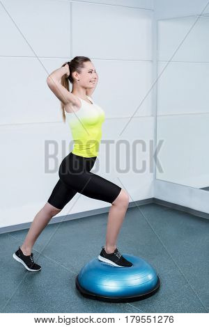 Photo of beautiful young sporty woman. Fitness girl working out with bosu at fitness club