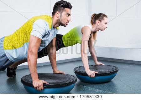 Photo of young sporty woman and man. Fitness people working out with bosu at fitness club