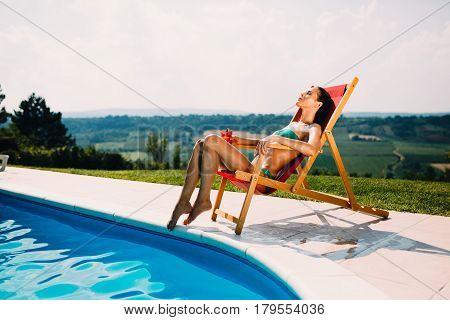 Beautiful woman enjoying summer and tanning at pool