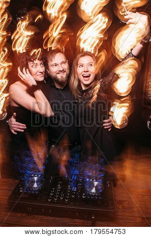 Two adult girls having fun clubbing, dancing and making selfie on phone with handsome disk jockey at DJ console. Bright long exposure of light.