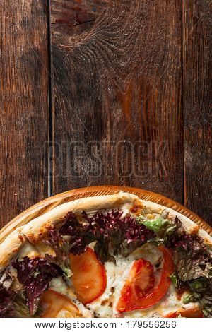 Yummy italian pizza served on wooden background at the bottom with free space for text. Fast food restaurant photo.