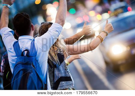 Group of friends hailing cab at night in city