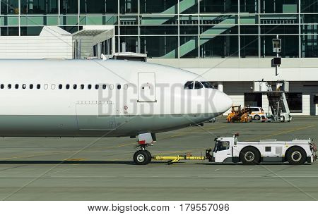 Tug Pushback Tractor With Aircraft On The Runway In Airport.