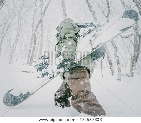 Unrecognizable freerider young man with snowboard walking in winter forest among snowdrifts close-up