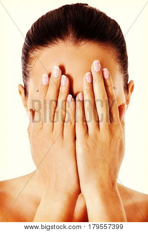 Young woman covering her face with her hands.