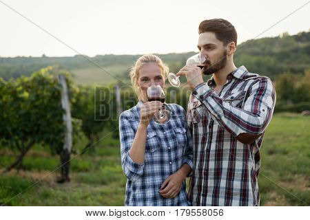 Beautiful woman tasting wine in wine grower vineyard