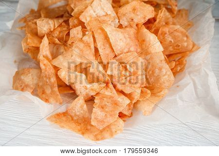 Junk food, unhealthy eating, cholesterol, calories. Potato chips on white paper, closeup. Unwholesome fast food, beer snack
