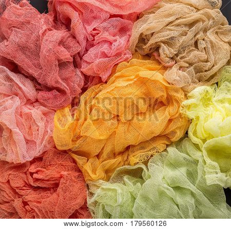 Multicolored background of red orange yellow lemon and crimson colors of gauze fabric