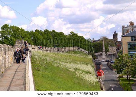 York Yorkshire England UK - May 22 2016 : Tourists walking along York City Roman wall surrounding the City