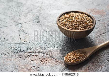 Spelt on the dark grey stone table in a wooden bowl selective focus