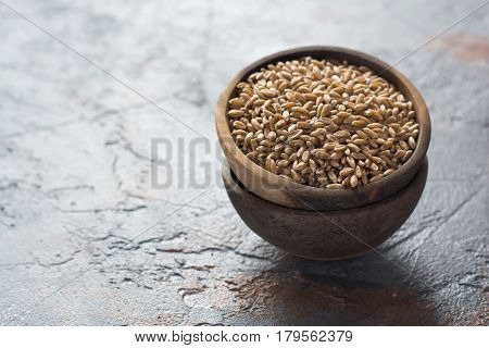 One of the ancient cereals spelt on the dark grey stone table selective focus