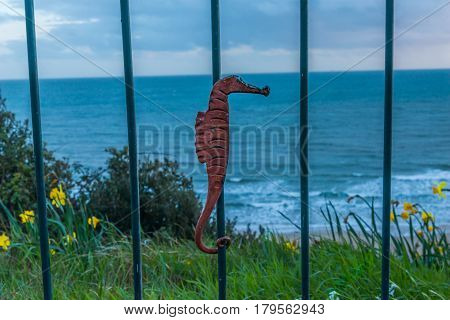 Metal Ornament On A Balustrade In A Seaside Village, Symbolic In The Shape Of A Seahorse