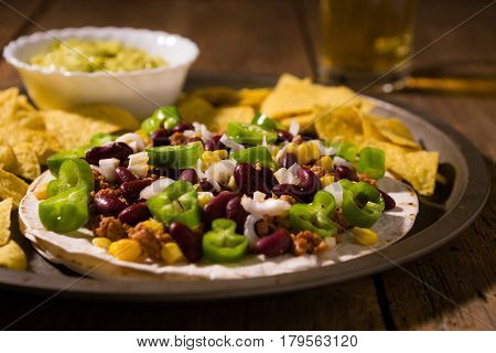 Mexican tortillas with meat red beans Jalapeno pepper and nachos chips over an old wooden table