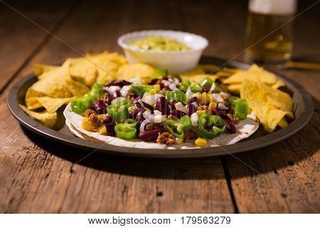 Mexican tortillas with meat red beans and Jalapeno pepper over an old wooden table