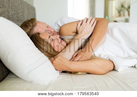 Romantic young couple in bed being intimate