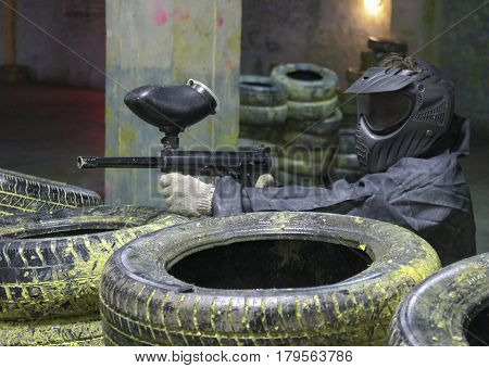A man with a marker for paintball in the woods sitting for tires in the ambush.
