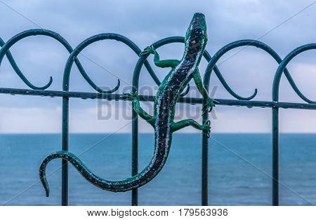 Metal Ornament On A Balustrade In A Seaside Village, Symbolic Lizard-shaped Element