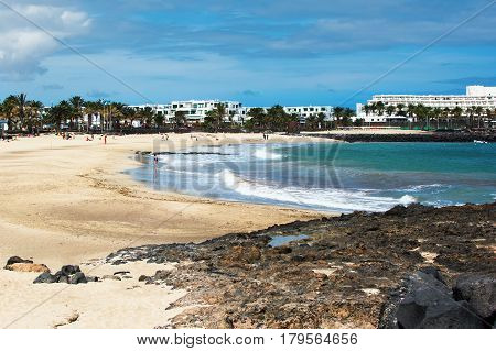 Costa Teguise beach with golden sand and blue sea volcanic stones Lanzarote Spain selective focus