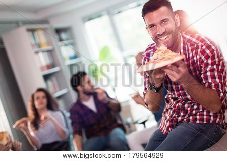 Coworkers eating pizza during work break at office