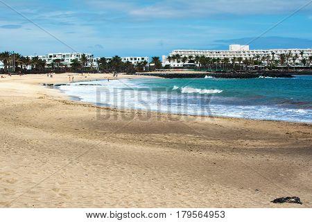 Golden sand and blue sea in Playa de las Cucharas beach in Costa Teguise Lanzarote Spain selective focus