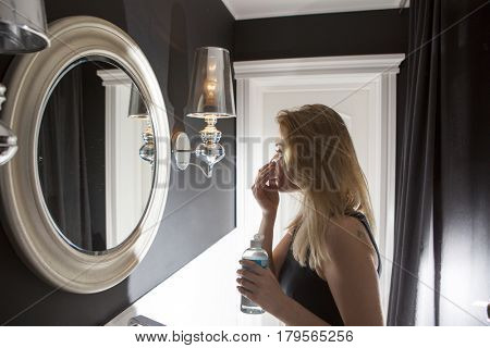Woman using a cotton pad to remove her makeup in the bathroom at night