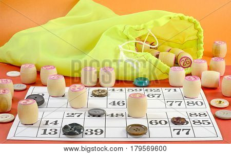 photo side view of details of Russian vintage game Bingo or Lotto with white paper cards in the cells which contain numbers small wooden barrel on which is written the numbers green bag multi-colored buttons on the table red color
