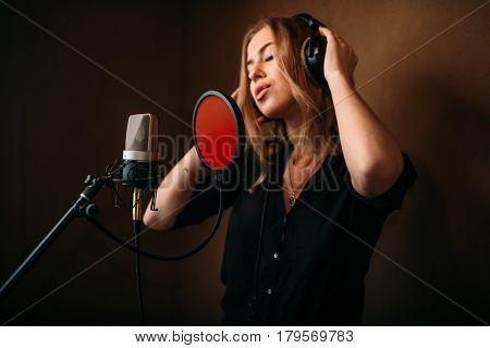Female singer in headphones against microphone
