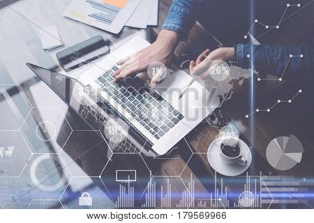 Businessman working at sunny office on laptop while sitting at the wooden table.Concept of digital screen, virtual connection icon, diagram, graph interfaces on background.Blurred, visual effects