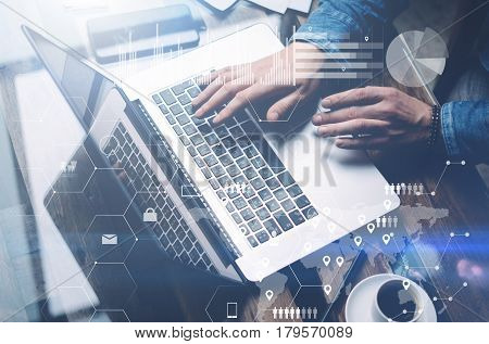 Concept of cyber security.Man working at sunny office on laptop while sitting at the wooden table.Background of digital screen, virtual worldwide connection icon, diagram, graph interfaces.Blurred