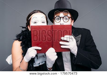 Two comedy performers posing with book