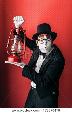 Pantomime actor performing with kerosene lantern