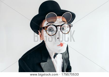 Pantomime actor face in glasses and makeup mask