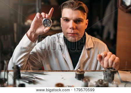 Watch maker holding wrist watch in hand