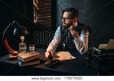 Bearded writer in glasses smoking a pipe