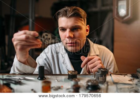 Watchmaker holding with tweezers a gear of hours