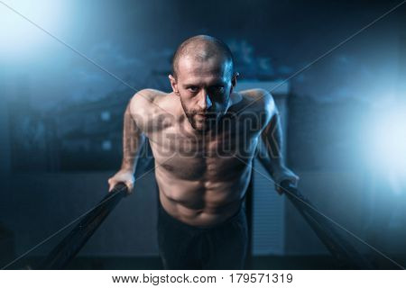 Muscle gymnast exercises on sports bars in gym