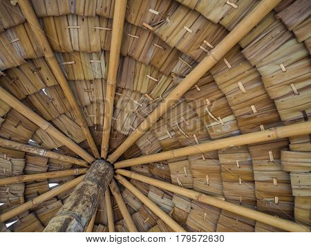 under thatched roof inside closeup bamboo structure