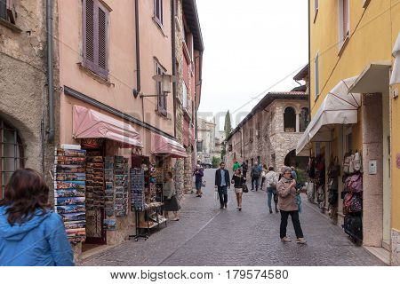 Tourists Walk The Streets And Inspect Local Attractions In Sirmione