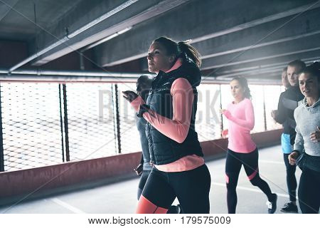 Attractive athletic woman urban running with a group of diverse young friends sprinting through a commercial undercover car park in a close up view