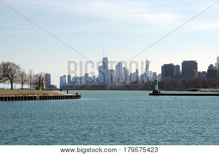 Chicago Skyline as seen through Montrose Harbor entrance waterway with lighthouse on the side under a blue sky
